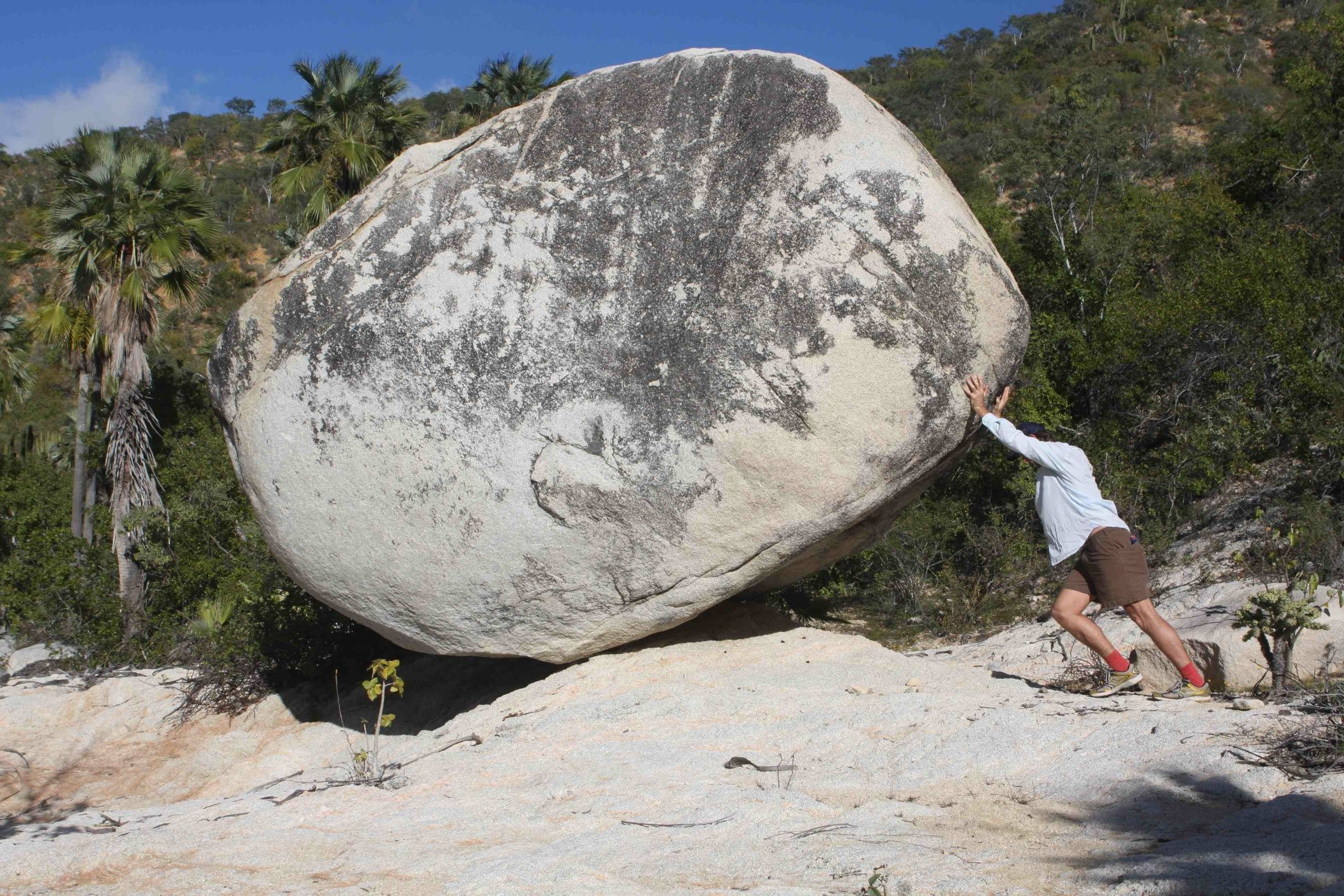 Man pushing a boulder uphill